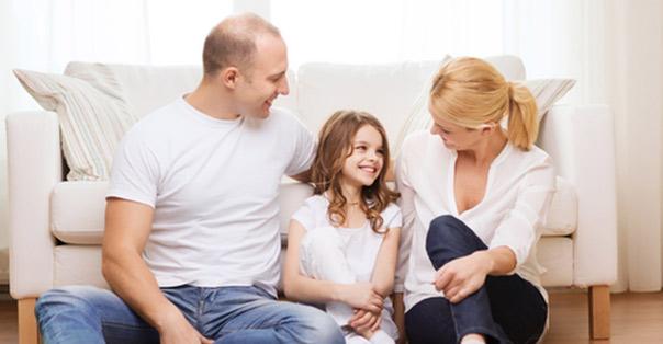 Foreldre sitter med barnet i mellom seg og smiler