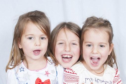 Tre søsken smiler