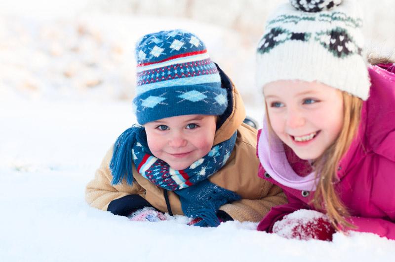 Jente med lillebror i snøen, smiler
