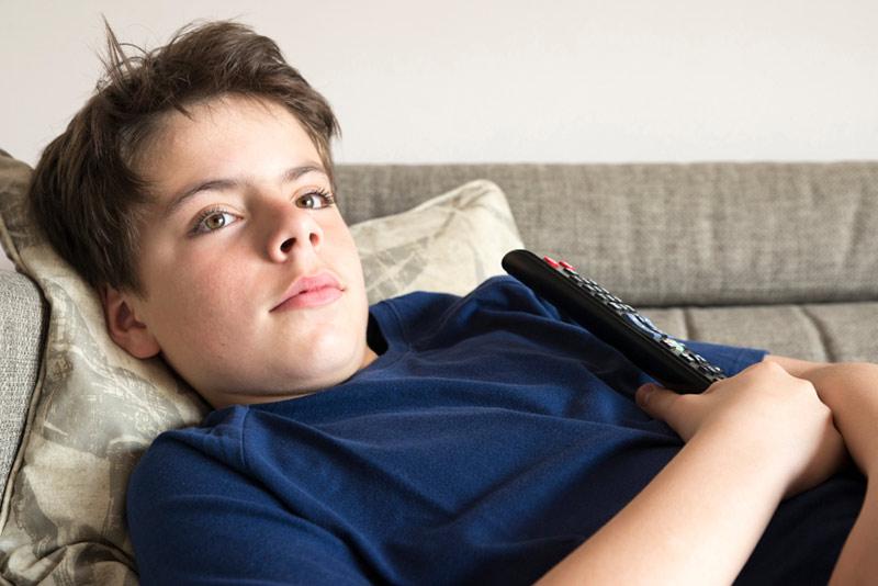 Gutt som ligger på sofaen og ser på TV