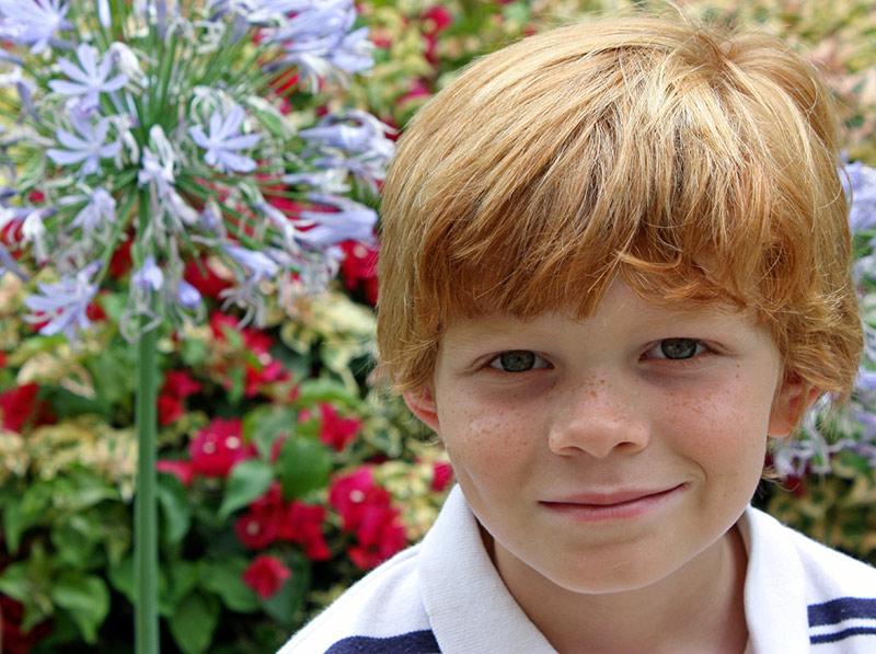 Gutt med rødt hår smiler, blomster i bakgrunn