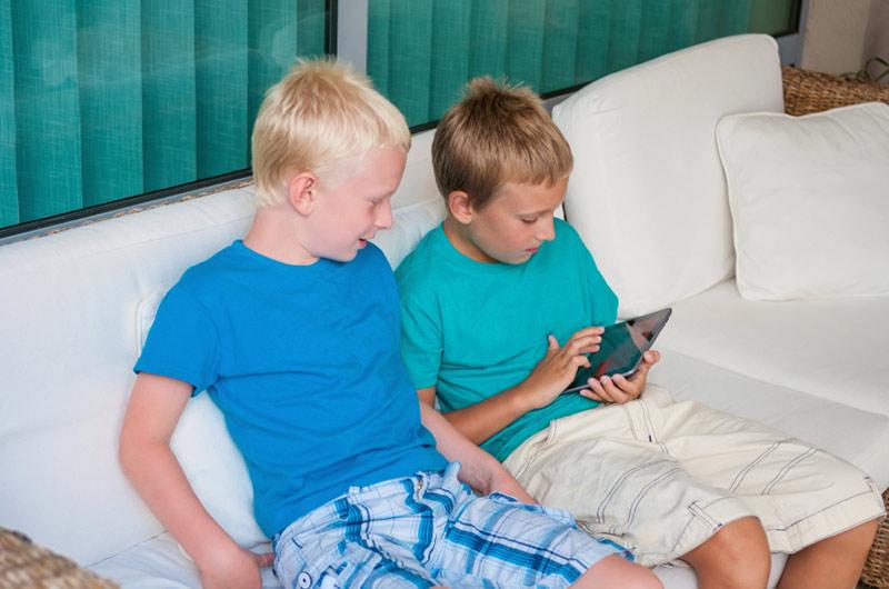 To gutter spiller nettbrett i sofa