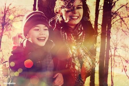 Mor og sønn ler og smiler. I skogen.