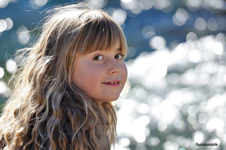Jente 8 år smiler til kamera