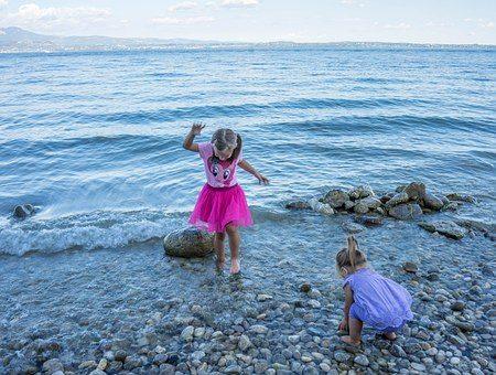Søsken leker sammen på stranda