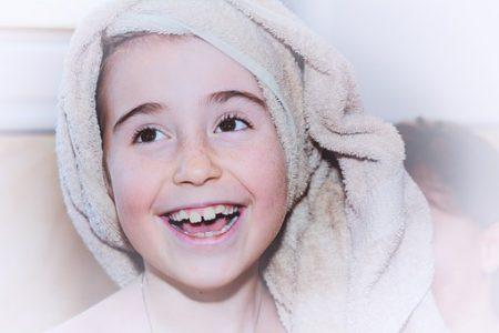 Jente med håndkle på hode smiler