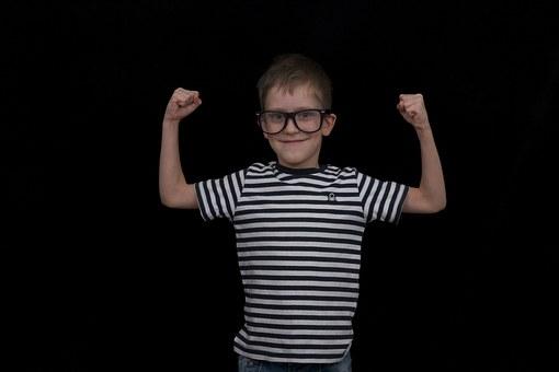 Gutt som smiler og viser musklene