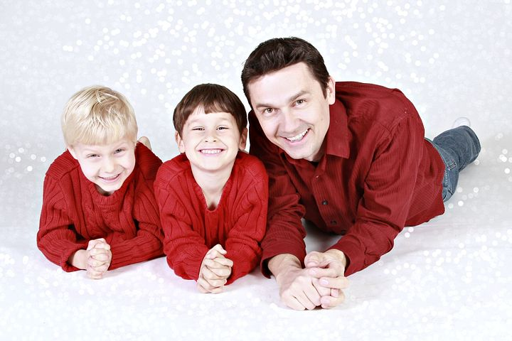 Familiebilde av to smilende sønner og far