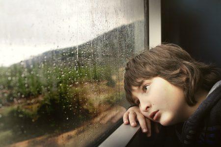 Trist gutt ser ut av vindu