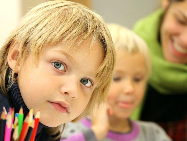 Gutt ser alvorlig inn i kamera, med lærer og medstudent i bakgrunn