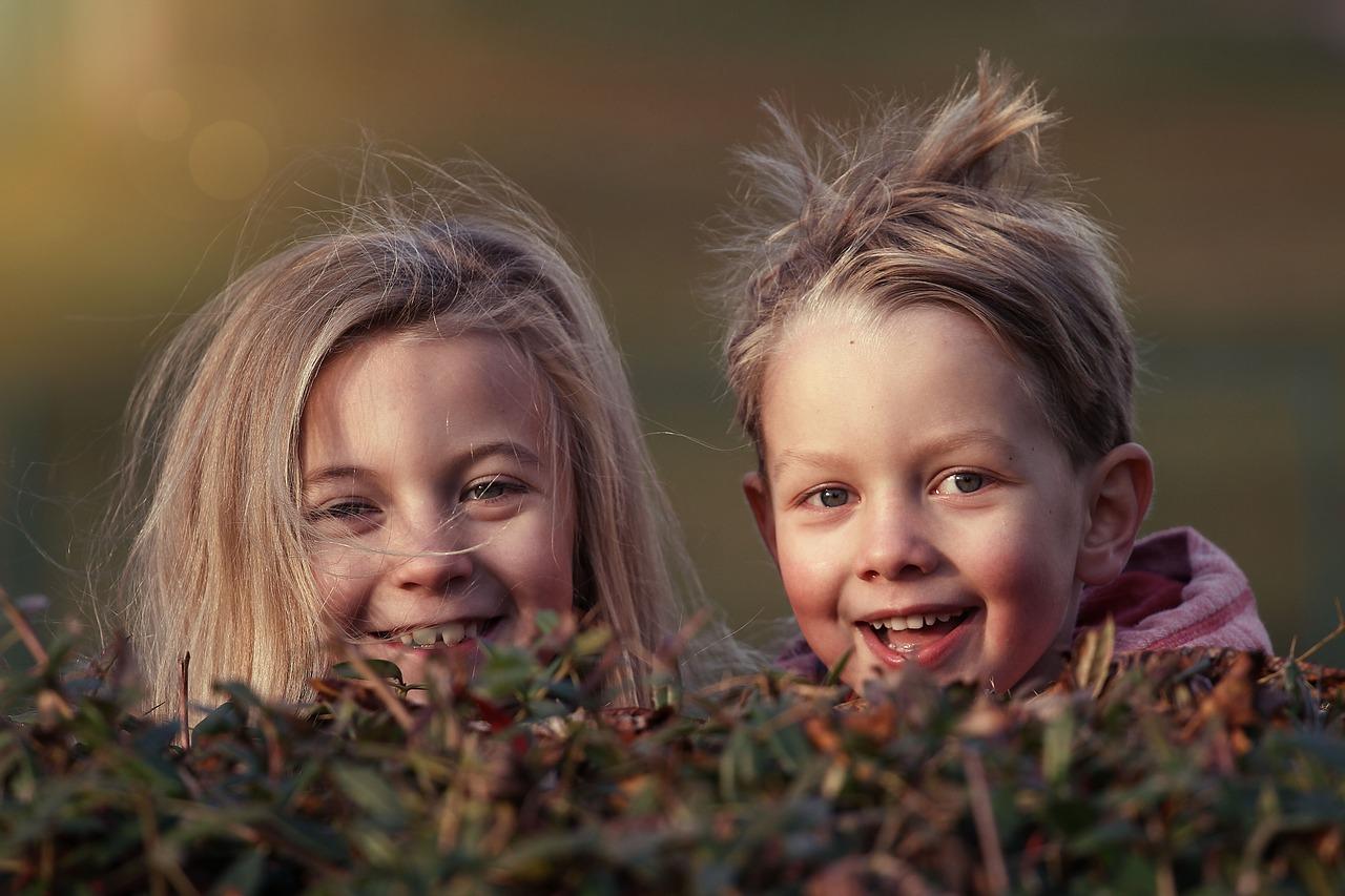 Søsken smiler fra bak en busk og har bustete hår