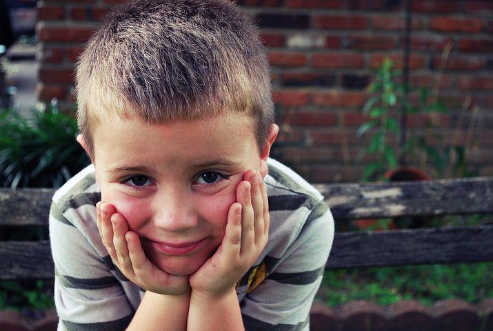 Gutt smiler, men gjemmer ansiktet imens han lener ansiktet på hendene