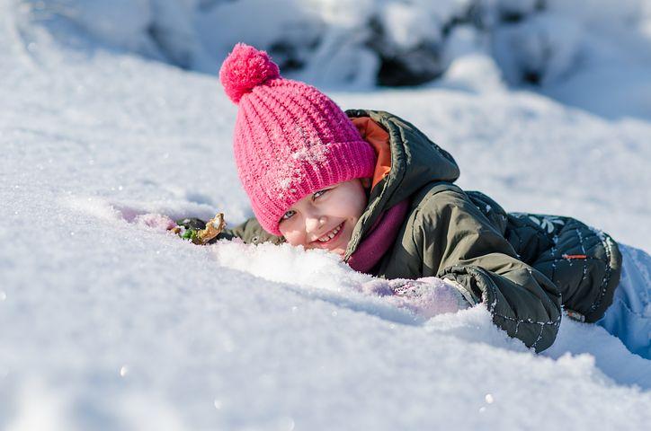 Jente ligger på snøen og smiler