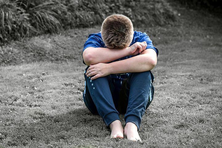 Gutt som ser ned og gjemmer seg i en omfavnelse