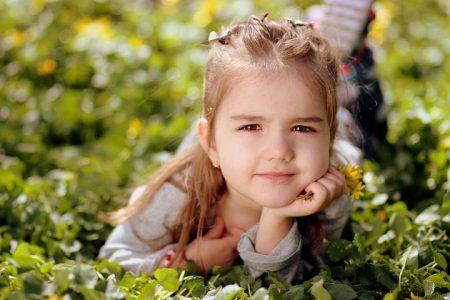 Jente ligger på gresset og tenker