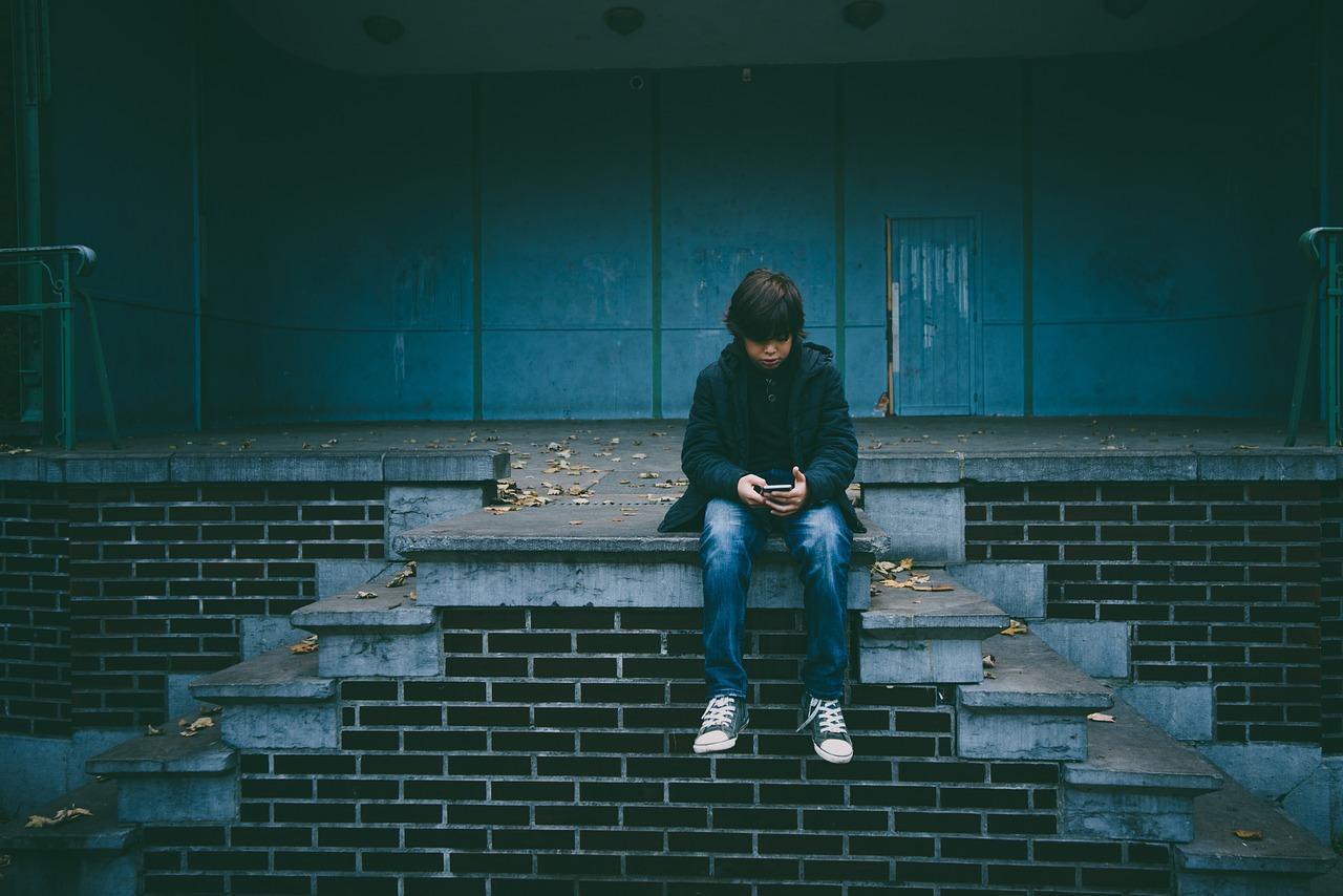 Gutt ser ensom ut, ser ned på mobilen