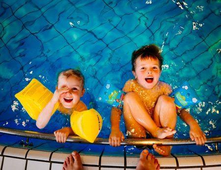 To søsken bader i basseng og smiler opp til kamera
