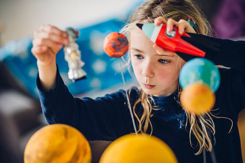 Jente leker med planeter og andre romfigurer