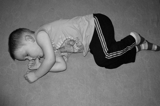 Gutt sover med tommelen i munnen