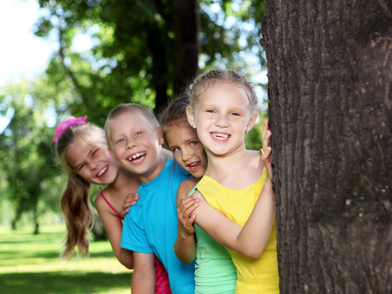 Glade barn bak et tre