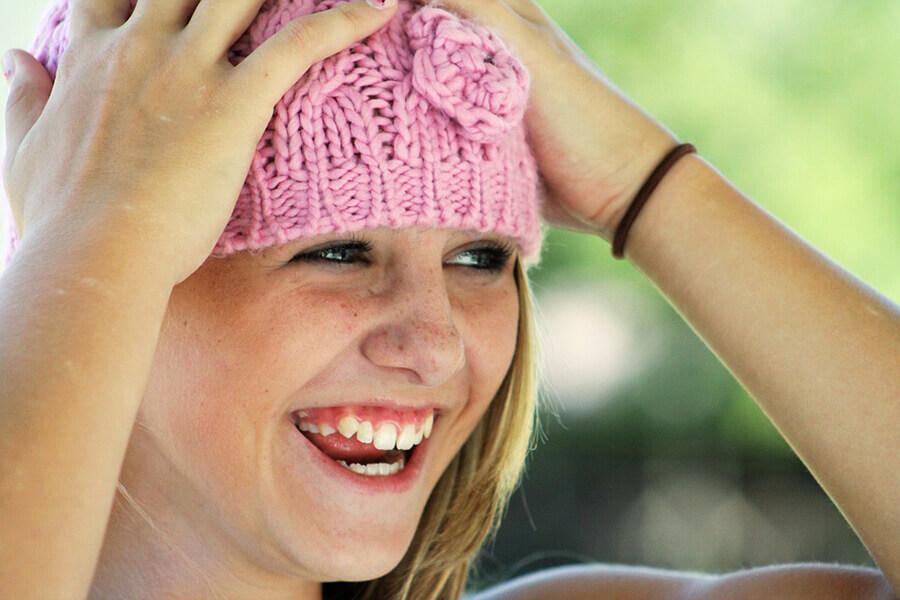 Jente med rosa lue, smiler