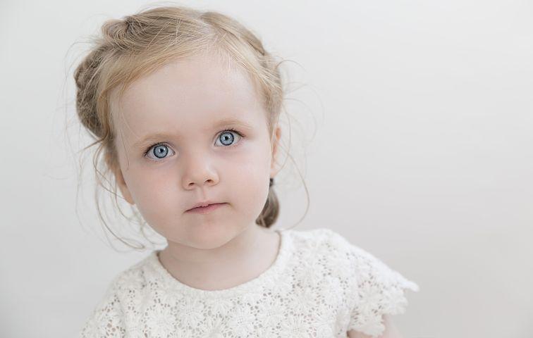 En jente med store blå øyne og ser alvorlig ut