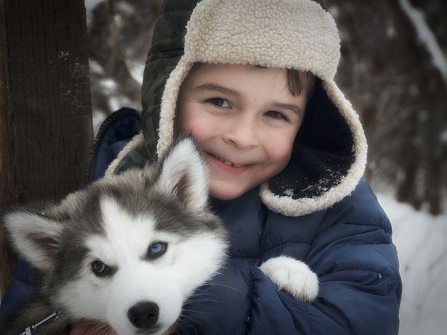 Smilende gutt holder en husky valp