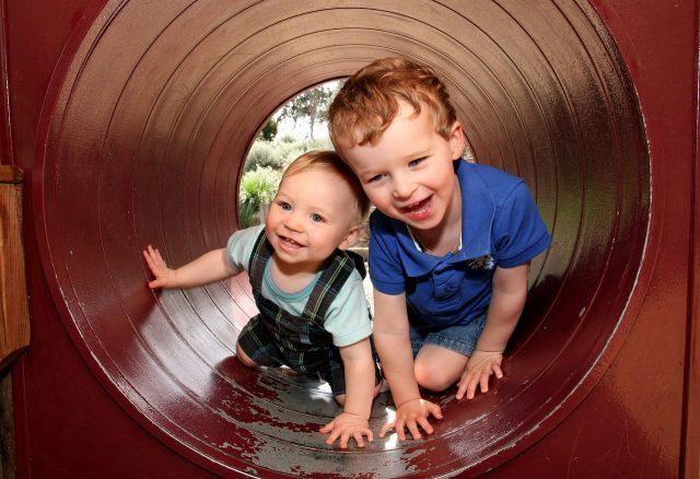 To brødre klatrer igjennom leketunnel