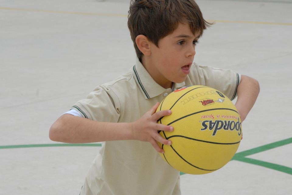 Gutt har ballen i basketballkamp