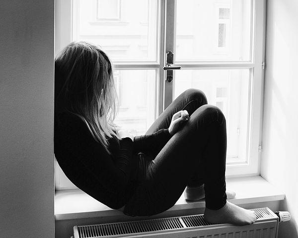 Jente gjemmer seg i vinduskarm
