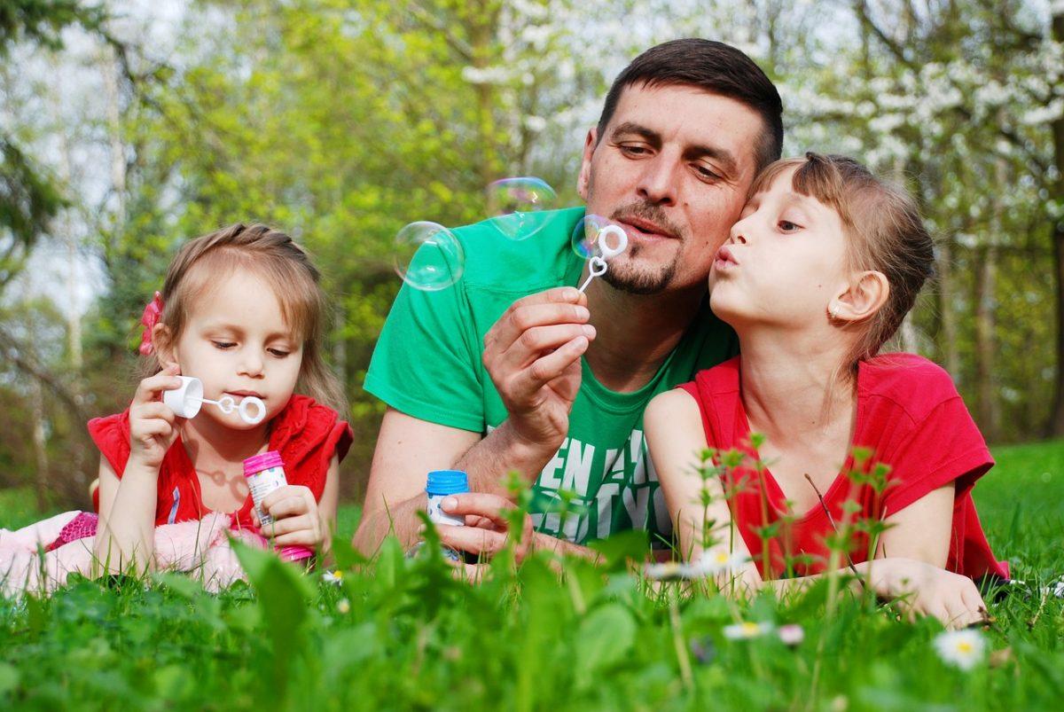 Far blåser bobler med to døtre