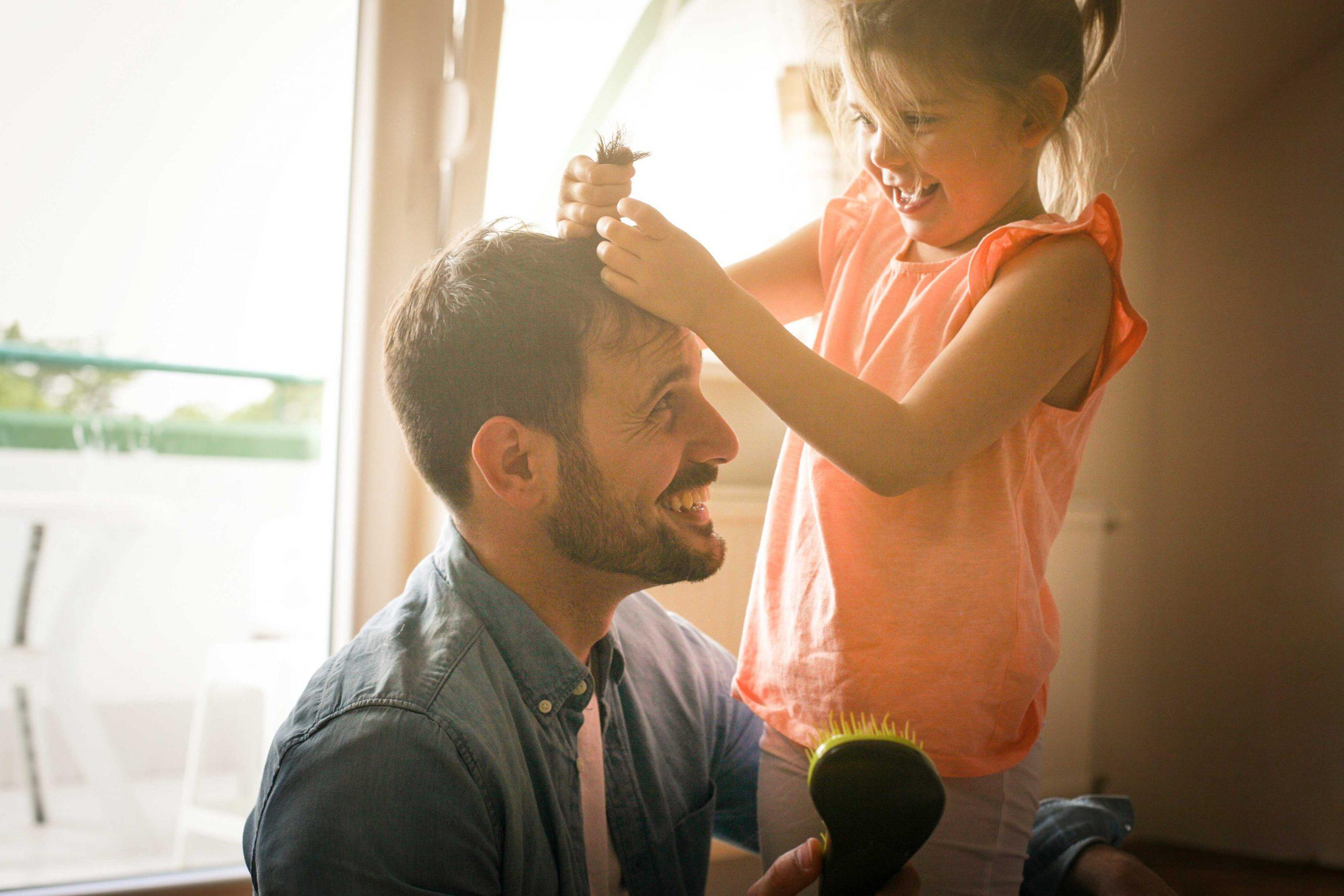 Jente setter strikk i håret til faren sin. De smiler og ler.