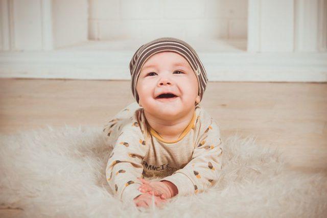 Baby ligger på teppegulv og smiler stort