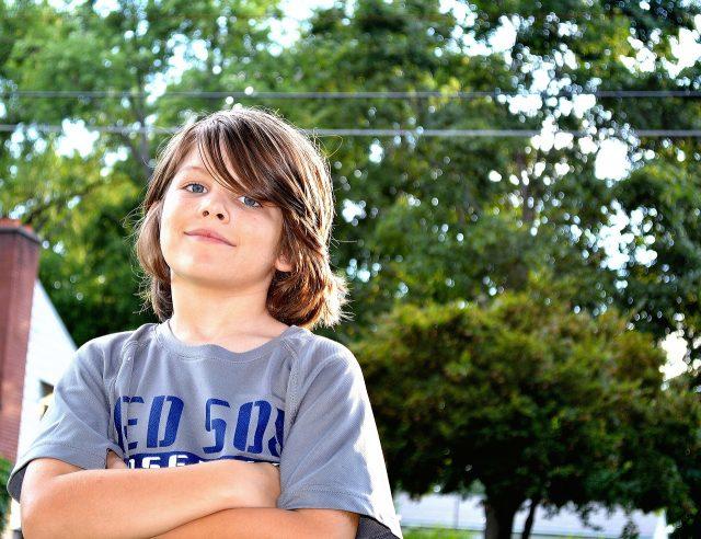 Gutt 10 år holder armene i kors og ser lur ut.