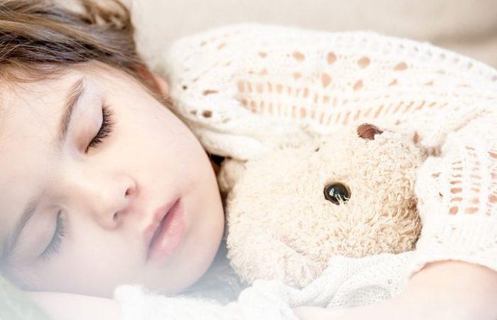 En liten jente sover med bamsen sin
